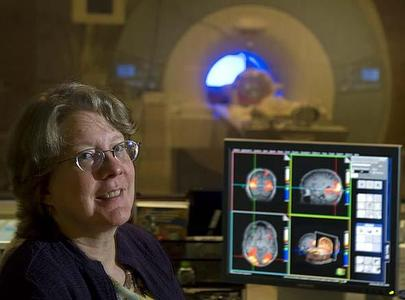 The sound of a functional magnetic resonance imaging machine, shown with study author Cheryl Grady, distracted older adults in the memory test.