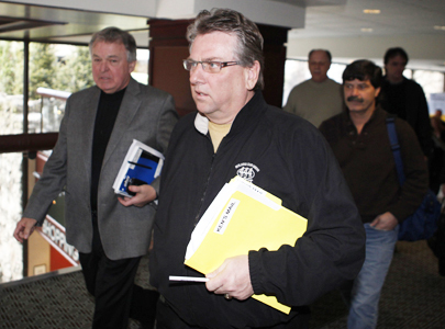 CAW president Ken Lewenza, centre, leaves after speaking to media in Toronto on March 30, 2009. Automakers are in talks over deeper cuts.