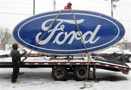 Workers secure a Ford sign onto a truck after it was removed from Al Long Ford auto dealership in Warren, Michigan December 23, 2008.