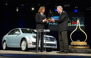 Angus MacKenzie, left, Motor Trend Magazine editor-in-chief, hands the trophy for Car of the Year to Ford Group Vice President Derrick Kuzak. (Bryan Mitchell / Special to The Detroit News)