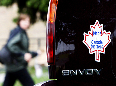 Woman walks by bumper sticker to buy Canadian in Oshawa June 1, 2009 as GM files for bankruptcy protection in New York
