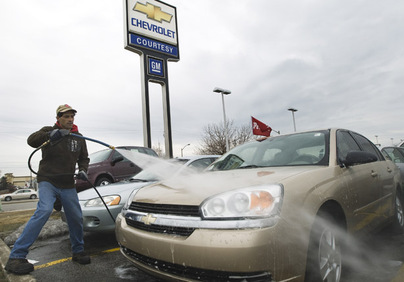 An employee at a GM dealership washes cars in Toronto, March 5, 2009.