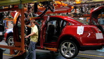 A worker checks on a 2010 Ford Taurus on the assembly line at the Ford plant in Chicago. The plant has been retooled to build the vehicle. Frank Polich/REUTERS