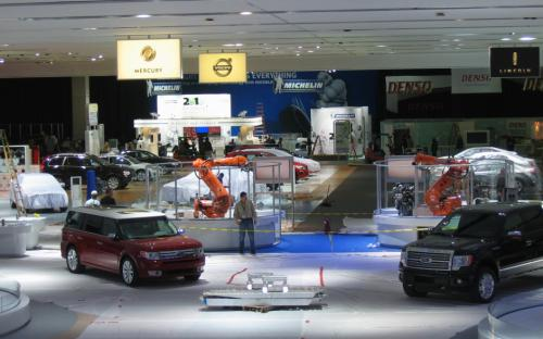 Ford sets up its expanded show stand amid plastic sheets, coiled extension cords and flashing electronic signs.