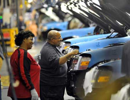 Ford employees Monica Stephens, left, and Michael Mathis help a row of 2010 Ford Explorers move through final assembly at a Louisville, Ky., plant Thursday. Ford will add 1,800 workers and invest $600 million in the plant, which will make the next-generation Ford Escape and other vehicles. (Sam VarnHagen / Ford)