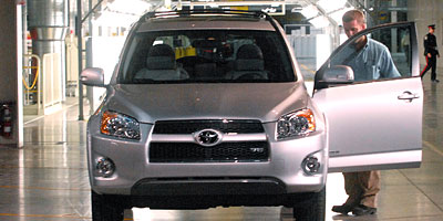 "A Toyota employee opens the door of a new Toyota RAV4 after the car rolled off the production line at the grand opening of Toyota Motor Manufacturing Canada's ""greenfield"" plant in Woodstock, Ont., on Dec. 4, 2008."