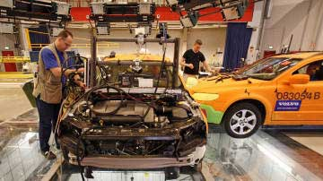 Technicians prepare vehicles for a test crash at the Volvo Safety Centre in Gothenburg, Sweden