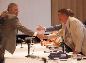 David Wenner, left, general director of labour relations for General Motors, shakes hands with Chris Buckley, chairperson of the CAW's GM master bargaining committee, in Toronto on Aug. 14, 2012