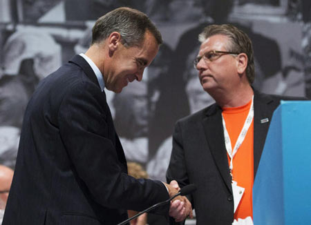 Bank of Canada Governor Mark Carney, left, and CAW National President Ken Lewenza, right, shake hands at the Canadian Automotive Workers' First Constitutional and Collective Bargaining Convention in Toronto on Wednesday.
