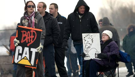Anna Wittich, left, with sign, and Magdalena Schoenmakers, seated, join locked-out Electro-Motive workers on the picket line Friday in London, Ont. The Caterpillar plant's unionized workers were locked out of the factory Jan. 1, 2012.