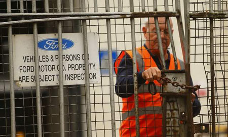 A security guard locks a gate after workers left the Ford Transit Assembly Plant in Southampton, England after being told that the site will close. (Chris Ison/PA/Associated Press)