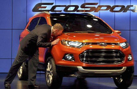 Ford CEO Alan Mulally kisses the new EcoSport, among the vehicles Ford is expected to launch this year in China. (Associated Press