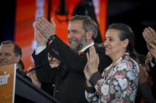 New NDP leader Thomas Mulcair, left, and his wife Catherine Pinhas applaud after Mulcair won the contest to become party leader in Toronto on Saturday.