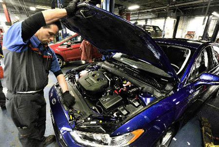 Service technician Rich Rushlow examines the popular 2-liter EcoBoost engine in a 2013 Ford Fusion at Village Ford in Dearborn on Friday. (Daniel Mears / The Detroit News)