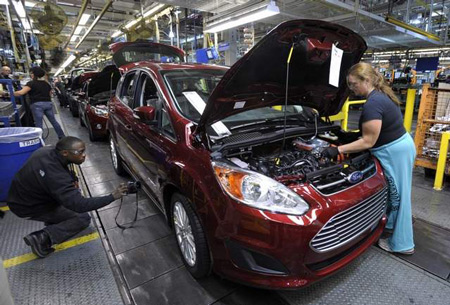 Workers make final tweaks to a C-Max Hybrid at the assembly plant in Wayne. Ford is on pace to sell a record number of electrified vehicles. (Todd McInturf / The Detroit News)