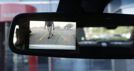 A new surveillance system that displays on the rear view mirror in police cars automatically sounds a chime, locks the doors and rolls up the windows if it detects someone approaching the car from behind. (Carlos Osorio/AP)