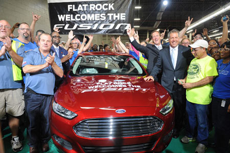 From left, foreground, Tony Bondy, United Auto Workers Local 3000 chairman; Jimmy Settles, UAW vice president; Tim Young, plant manager, and Joe Hinrichs, president of Ford of the Americas, and a group of UAW line workers launch production of the 2014 Ford Fusion at Ford's Flat Rock plant Thursday, Aug. 29, 2013. (Charles V. Tines / The Detroit News)