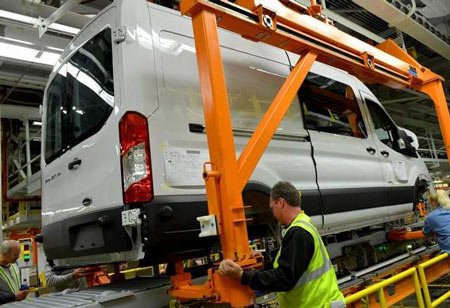 Mike Shearer works on a Transit at Ford's Kansas City Assembly Plant. It has multiple configurations, including three body lengths, two wheelbases, three roof heights and van, wagon, chassis cab and cutaway variations. (Sam VarnHagen / Ford Motor Co.)