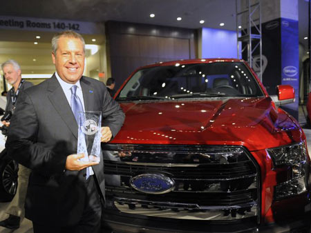 Ford Executive Vice President Joe Hinrichs shows off the award for Truck / Utility of the Year during day one of press previews at the North American International Auto Show in Detroit on January 12, 2015. (Photo: David Coates