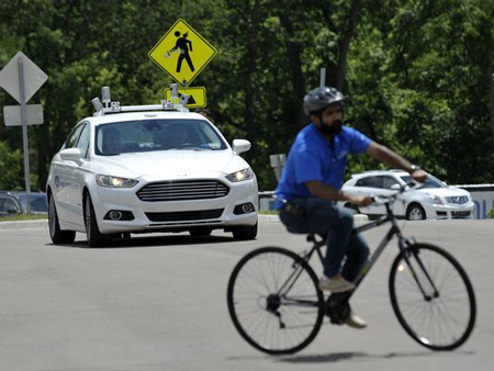 A Ford Fusion autonomous car waits for a cyclist to turn Wednesday at Mcity.