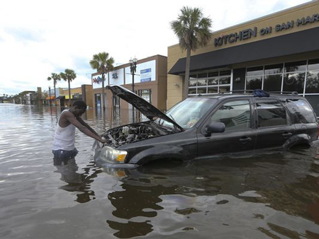 John Duke tries to figure out how to salvage his flooded vehicle in the wake Hurricane Irma this week. An estimated 200,000 to 400,000 vehicles were damaged by Irma.