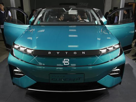 Invited guests and journalists listen to a staff member in the driver's seat of a BYTON electric concept car during a test drive event ahead of the Auto China 2018 automotive exhibition in Beijing, Sunday, April 22, 2018. The biggest global auto show of the year showcases China's ambitions to become a leader in electric cars and the industry's multibillion-dollar scramble to roll out models that appeal to price-conscious but demanding Chinese drivers.