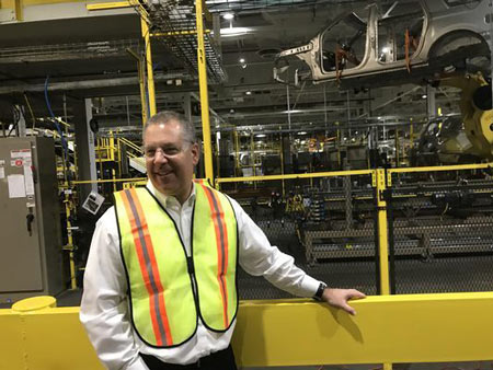 Ford President of Global Operations Joe Hinrichs stands in front of Kong, the robotic arm that places the bodies of Ford Expeditions and Lincoln Navigators on skids to roll down the assembly line in Ford's Kentucky Truck Plant on Feb. 9, 2018.