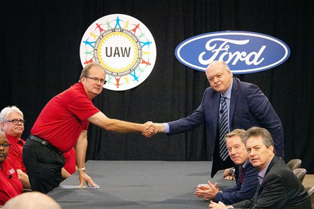 UAW President Gary Jones and Ford CEO Jim Hackett shake hands to formally kick of 2019 contract negotiations.