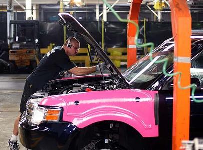 A Ford employee works under the hood of a Flex at the Oakville assembly plant Nov. 20, 2008. Canadian jobs are in peril as U.S. demand for autos stalls.