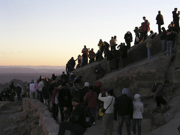 Pilgrims and hikers at the summit of Mount Sinai watch at dawn as the sun moves across the mountains and hills. Visiting far-off places, whether holy or not, can have a spiritual effect on any of us simply by impacting our view of the world.